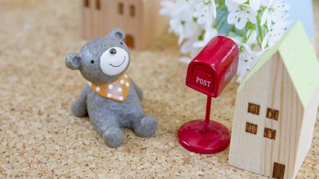 ポストの横で手紙を待つクマ