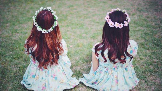 草原に座って後ろを向いている女の子2人