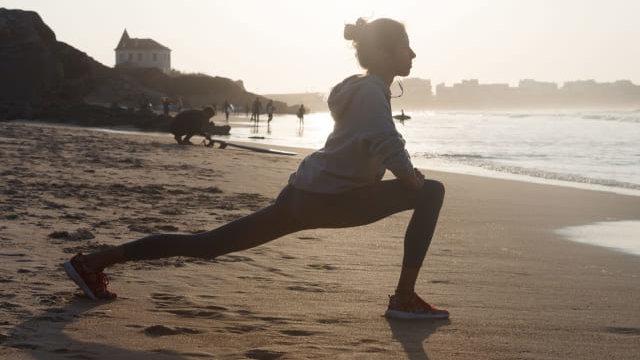 砂浜でストレッチする女性
